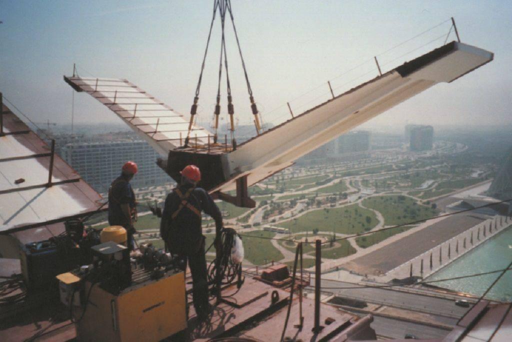 Deux techniciens sur un toit soulèvent des matériaux grâce à une grue et des outils Enerpac