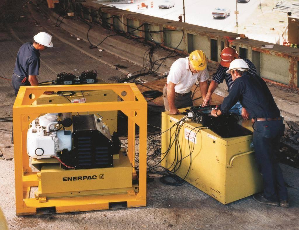 Quatre techniciens sur un pont utilisent une machine Enerpac
